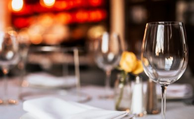 A close up shot of a restaurant table set up with tableware and wine glass. Concept of dining, hospitality and catering. Horizontal image with free space for text.